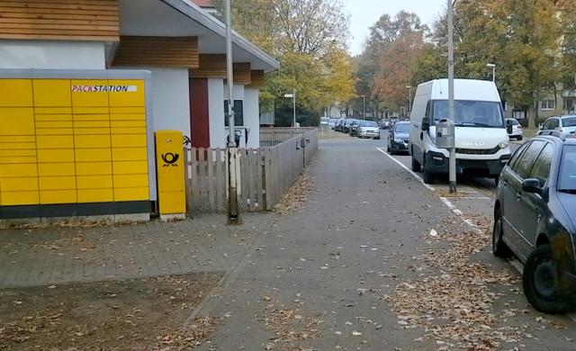 Blick auf die Sven-Hedin-Str. und den Kindergarten. Nahaufnahme des Gehweges direkt vor dem Eingang. Der Gehweg ist schmal, zugeparkt und die Sicht für den fließenden Verkehr völlig verstellt.
