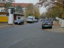 Blick auf die Sven-Hedin-Str. und den Kindergarten. Davor, beidseitiges Parken von Kraftfahrzeugen auf den Gehwegen.